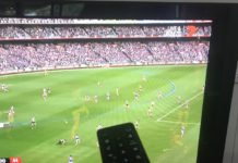 TV and TV Remote with footy showing